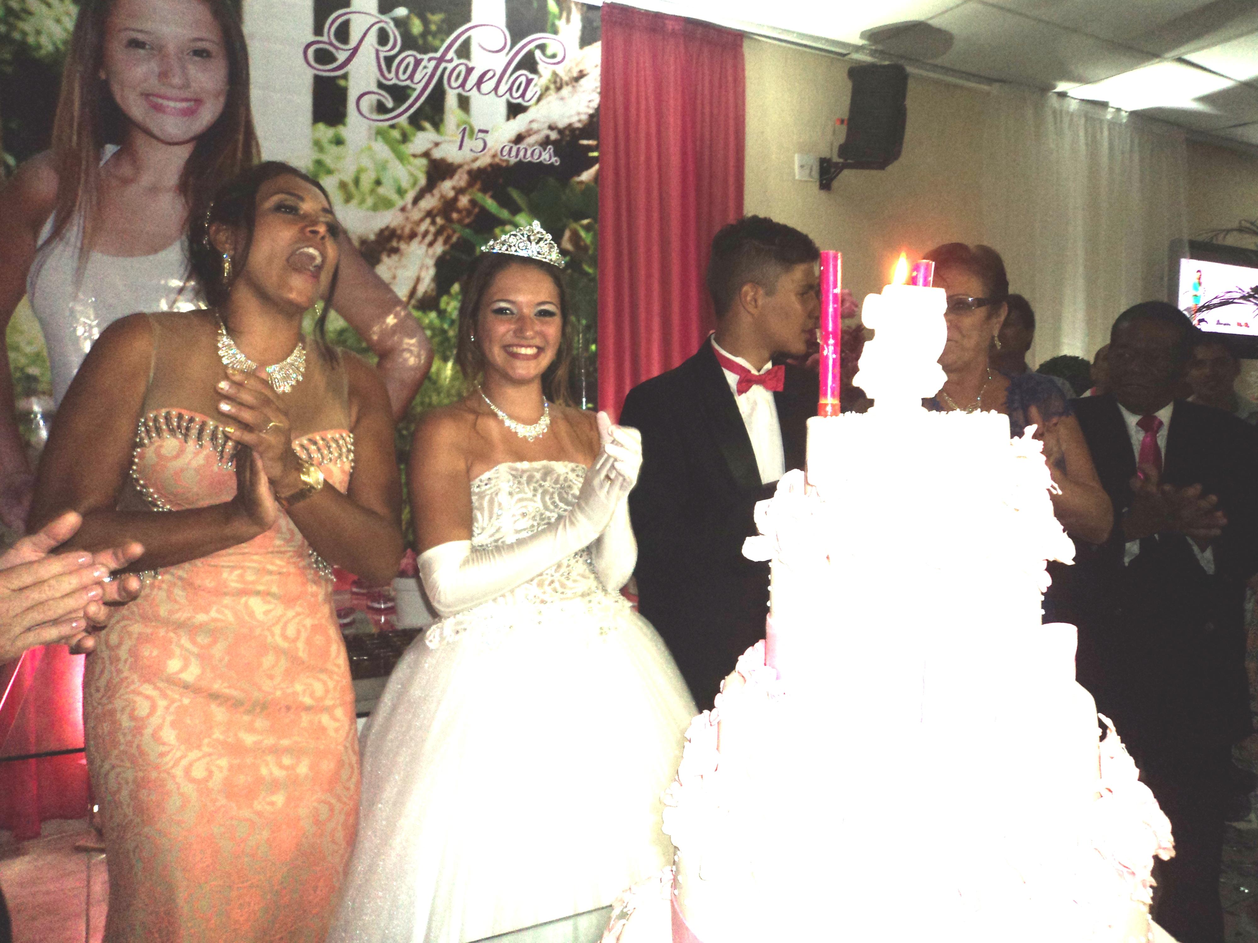 """Rafaela, na hora do """"parabéns para você"""" na mesa do bolo entre sua mãe e seu """"príncipe""""."""