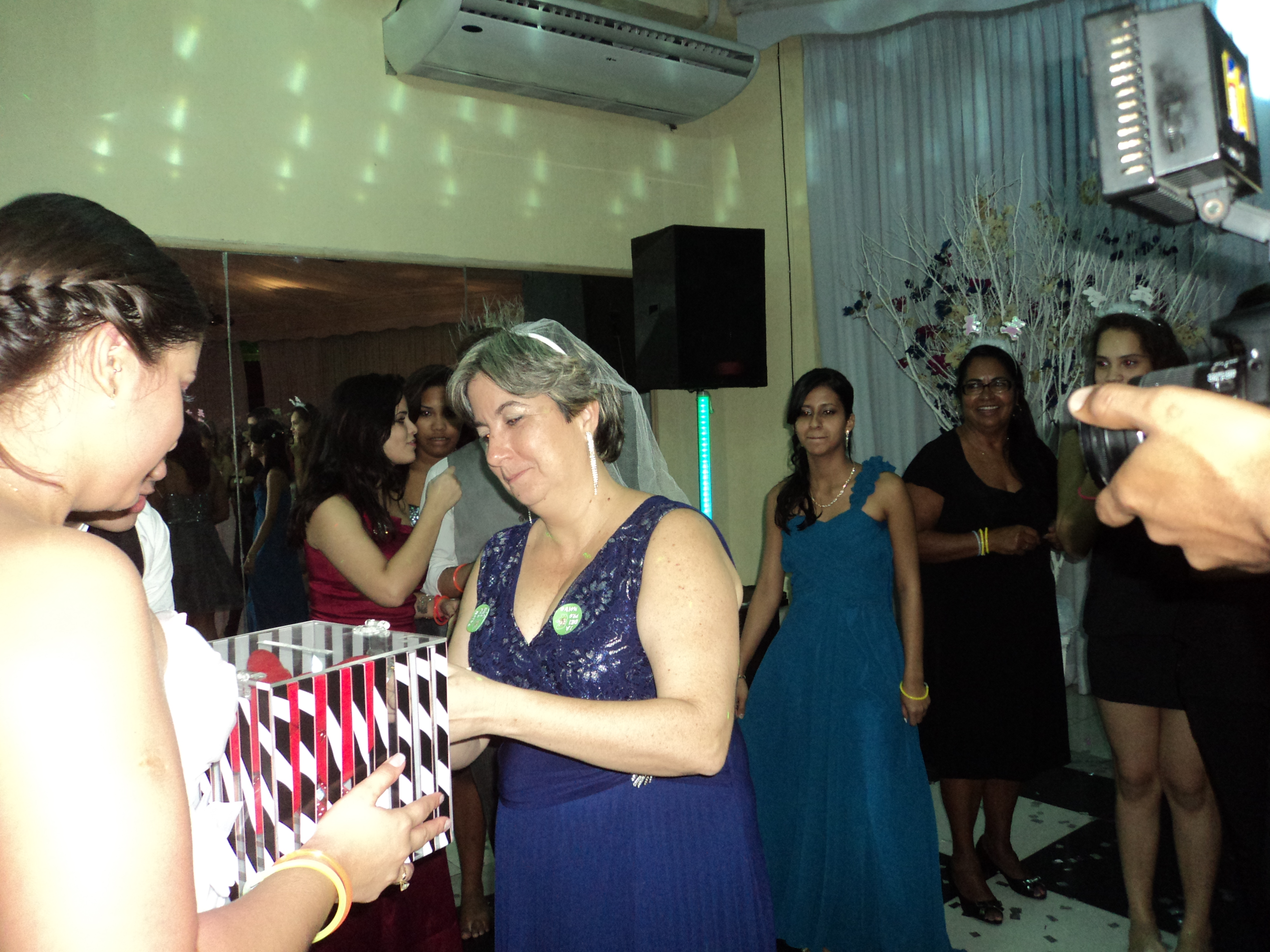 Foto da mãe do noivo abrindo o cadeado para ganhar o buquê da noiva.
