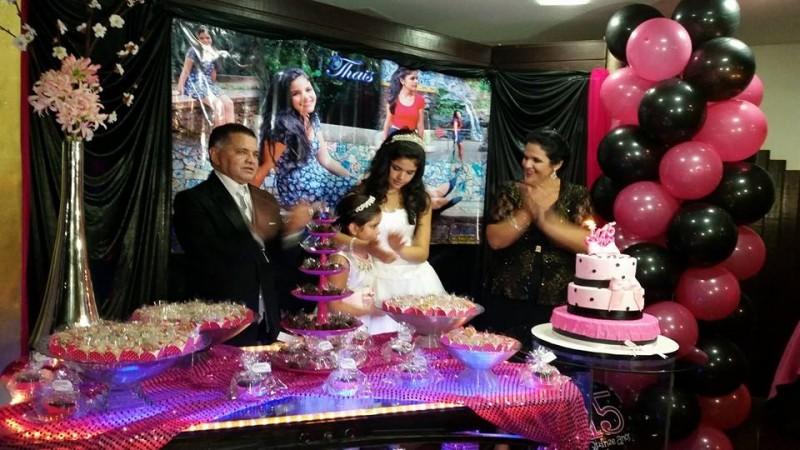foto da debutante Thais com seus pais e irmã na mesa do bolo