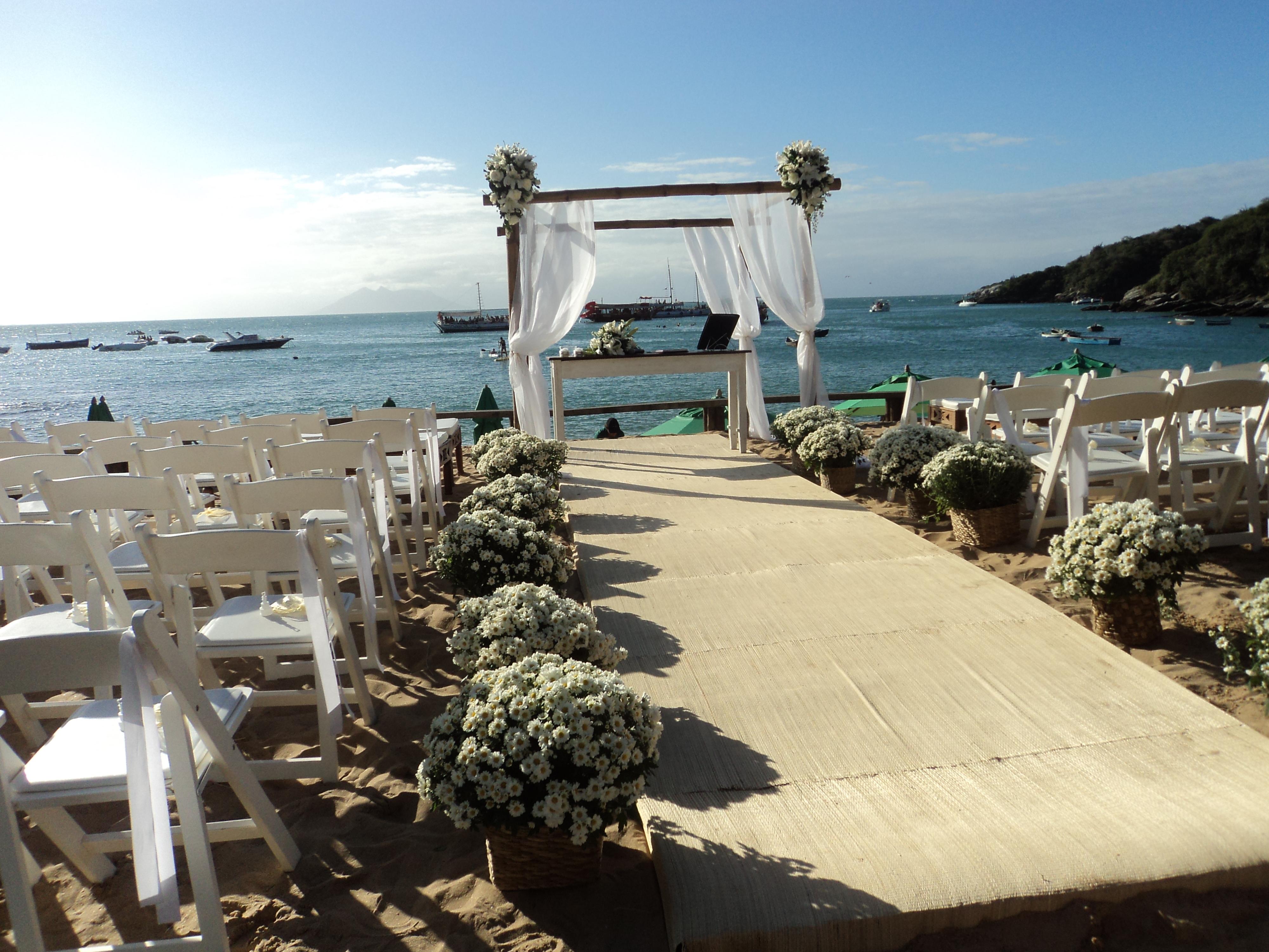 Foto dos noivos Joseph e Carol com Túlio de Pinho na praia logo após a cerimônia de casamento do casal.