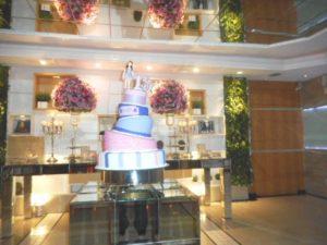 foto da mesa do bolo e doces ao fundo.